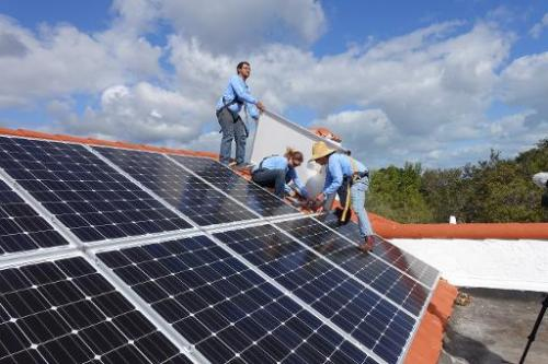 Workers install solar panels on a rooftop on February 20, 2015 at a home in Palmetto Bay, Florida