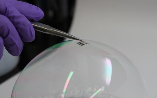 To demonstrate just how thin and lightweight the cells are, the researchers draped a working cell on top of a soap bubble, without popping the bubble. Photo: Joel Jean and Anna Osherov