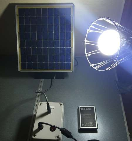 The prototype system consisting of a solar panel and 12V LED lamp wired to a battery pack containing three Samsung Galaxy Note 2 batteries. Credit: Diouf/Kyung Hee University